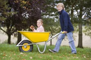 Boy pushing girl in wheelbarrow through autumn leaves