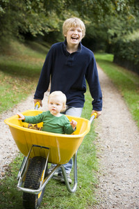 Boy pushing toddler in wheelbarrow through autumn woods