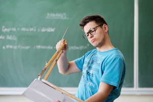 Boy with glasses holding a compass in front of a school blackboard