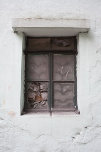Broken glass window in old wall of abandoned house