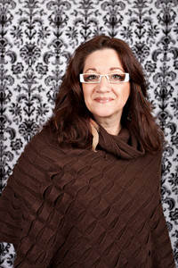 Brunette middle aged woman weather white framed glasses and feather hair extensions and accessories.