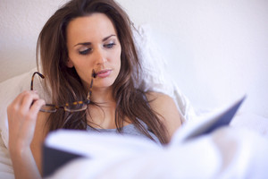 Brunette woman engrossed in reading a book while in her room
