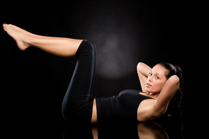 Brunette young Caucasian woman doing stretching exercise on the floor