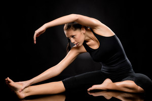 Brunette young woman exercising yoga in separate leg stretching pose