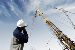 building worker pointing at construction crane