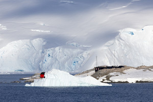 Buildings and a sunlit iceberg along a snowy coast