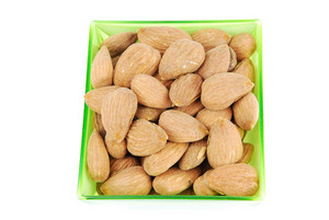 Bunch Of Almond Nuts On A Green Cup