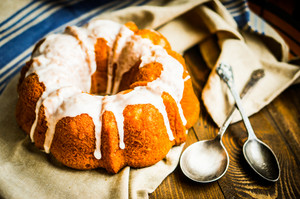 Bundt Cake With White Glaze On Rustic Background