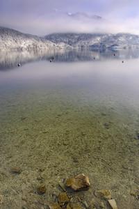 Buoys in a clear lake below a foggy mountain