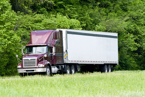 Burgandy Tractor-Trailer Rig On Interstate In Springtime