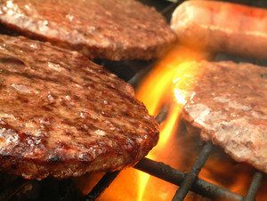 Burgers And Sausage Cooking On Barbecue