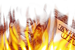 Burning American money with Benjamin Franklins face appearing on fire on a one hundred dollar bill.
