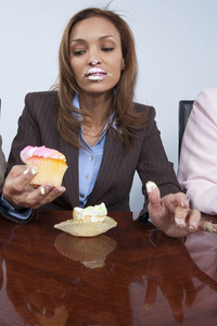 Business colleagues eating cupcakes in office