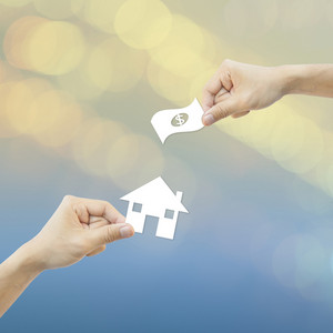Business concept Hand hold white paper house and money bokeh background.