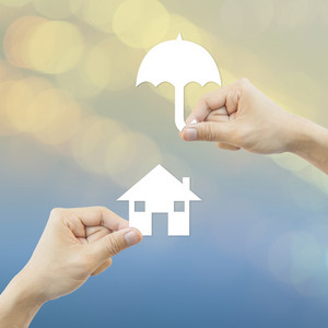 Business concept Hand hold white paper house and umbrella bokeh background.