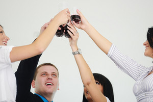 Business group celebrating a victory holding glasses with drink