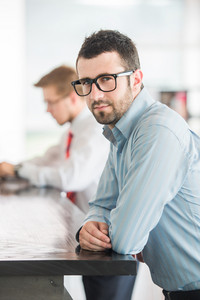 Business man posing leaning on a high table in company environment