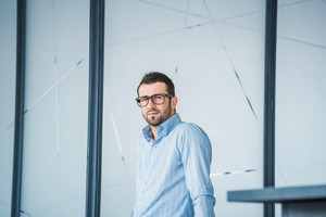 Business man with glasses standing in front of a glass wall