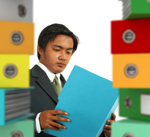 Business Manager Being Overworked By Office Paperwork