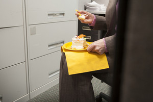 Business person eating birthday cake in cubicle