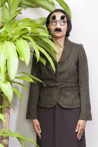 Business person hiding behind plant in office