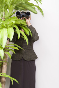 Business person with binoculars in office