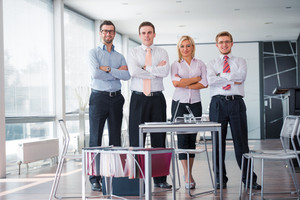Business team of four posing in a modern office