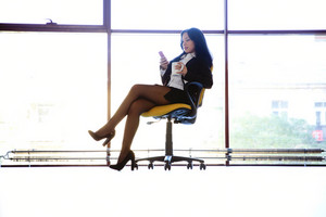 Business woman sitting in the chair with smartphone and cup with coffee at office