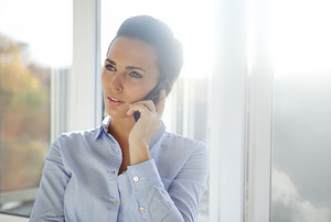 Business woman standing in a bright office while talking on her mobile phone looking away. Beautiful caucasian female model dressed in blue shirt.