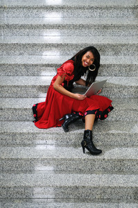Business woman with laptop on staircase