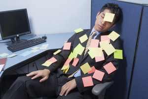 Businessman asleep at desk with notes