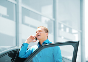 Businessman by the car car, talking on mobile phone, smiling