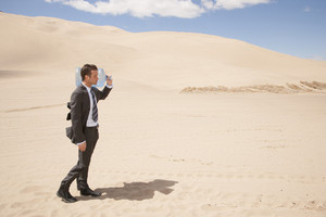 Businessman carrying water bottle in desert