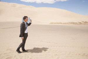 Businessman carrying water bottle in desert