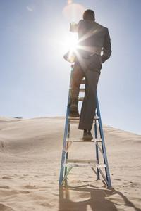 Businessman framing sun through fingers in desert