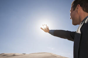Businessman framing sun through fingers in desert