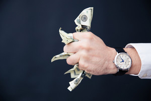 Businessman hand holding bills of US dollar in fist