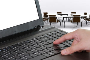Businessman Hands Typing On A Laptop With Meeting Room Background
