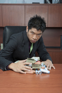 Businessman hoarding money