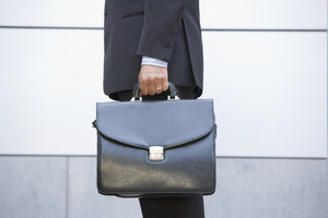 Businessman holding briefcase outdoors
