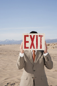 Businessman holding exit sign