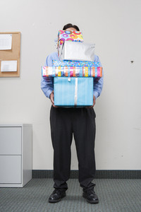 Businessman holding gifts in office