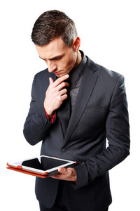 Businessman holding tablet computer and looking on it isolated on a white background