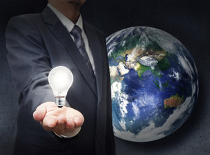 Businessman Holds Light Bulb To Glowing The Earth