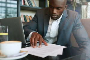 Businessman in a coffee shop reading a contract document. African business executive sitting at cafe working.