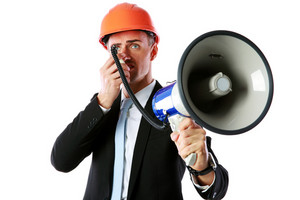 Businessman in helmet shouting with megaphone over white background