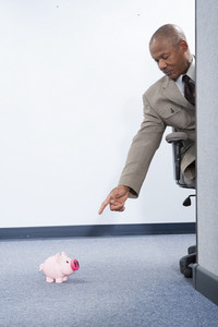 Businessman looking at piggybank