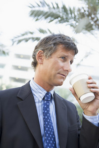 Businessman outdoors drinking coffee