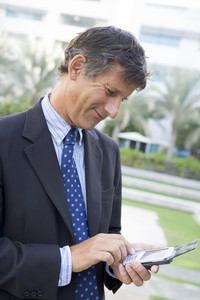 Businessman outdoors using personal digital assistant smiling