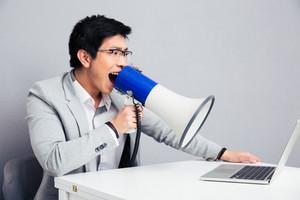Businessman screaming in megaphone on laptop